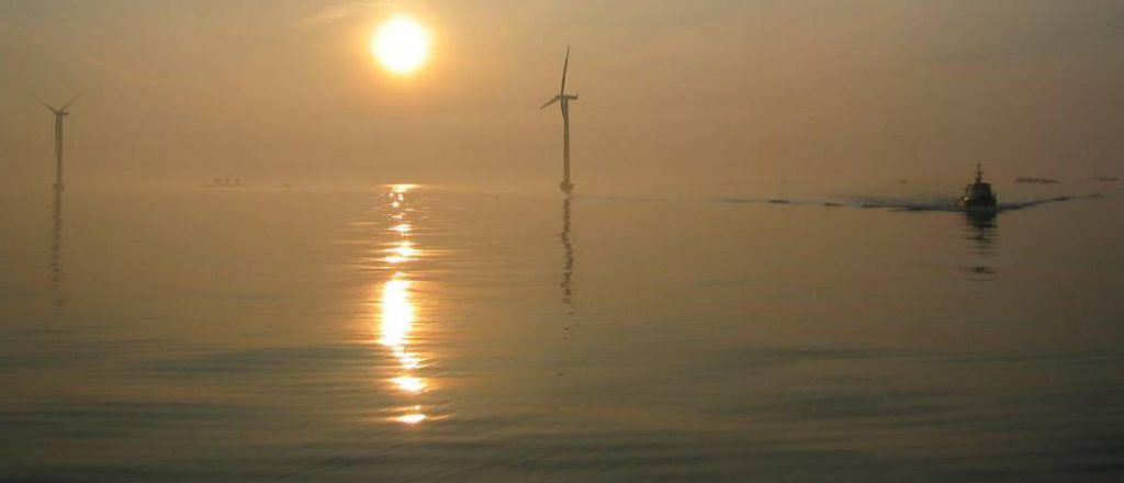 Off-shore wind mills and boat at sunset